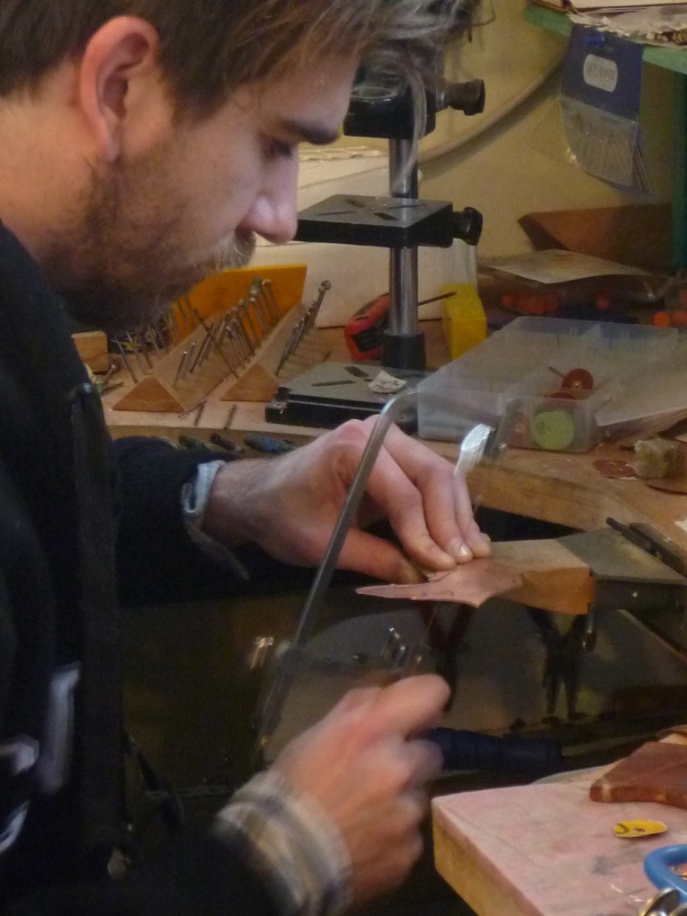 Jesse cuts metal and creates some jewellery.